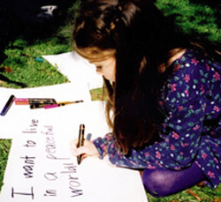PHOTO CREDIT: Marie Clarkson, OLM.  Thea Lewis writes her own placard message at a Toronto peace rally calling for an end to the war in Iraq. 2003.