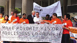 On June 29, 2006, supporters gathered in Toronto's Nathan Phillips Square to celebrate the first anniversary of the Live 8 concerts that shook two billion viewers worldwide and gave birth to the movement Make Poverty History (MPH) in 2005. MPH, the biggest ever anti-poverty campaign, aims to ROCK the leaders of the free world (the G8) into action and effect changes in aid, debt relief and the trade regulations that allow millions to suffer with disease and poverty. Mayor David Miller and Steven Page of the Barenaked ladies greeted the crowd with stories of progress and introduced local heroes from Toronto schools.  Photo and caption from Marc De Mouy of Grapevines – Downtown Toronto's Community Press