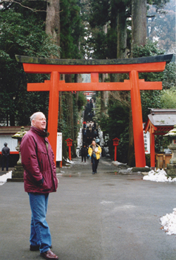 Fr. John Carten in front of the Torii Gate at the entrance of the Hakone Shinto Shrine in Hakone National Park outside of Tokyo.