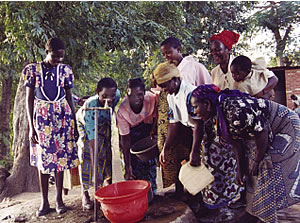 Filling their buckets at the communal water tap. St. Patrick's compound, Rumphi, Malawi.