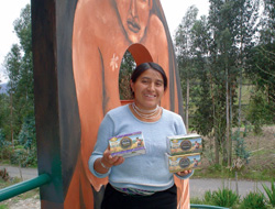 María Olivia, tea seller at Jambi Kiwa, with boxes of tea in front of the factory.
