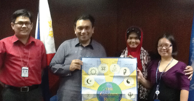 Muslim educator, Dr. Diampuan (second from right), shares Scarboro's Golden Rule poster with members of the Philippines Department of Foreign Affairs. L-R: Mr. Gary Domingo, Assistant Secretary for the UN and other international organizations; Mr. Gonar Musor, Director; and (far right) Ms. Bartolome, staffperson. Manila.