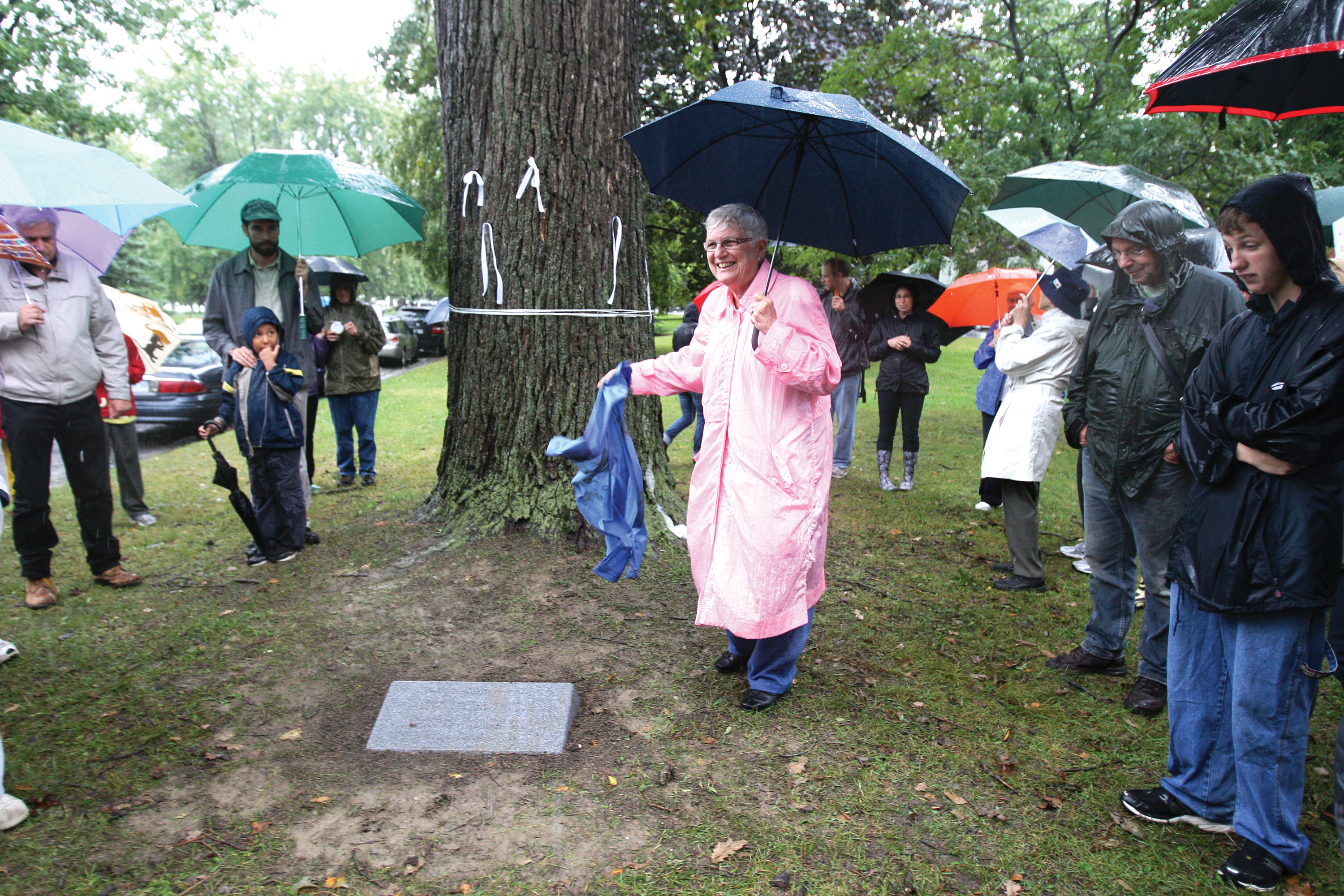"Sister Pauline Lally of the Sisters of Providence of St. Vincent de Paul unveils a message carved in stone beneath a 100-year-old oak tree at the official launch of PeaceQuest last year at the City Park in Kingston, Ontario, on September 21, the United Nations International Day of Peace. The inscription in each of Canada's official languages reads, ""Grieving the tragedy of war, committed to the promise of peace."" Last July, the mayor and city council of Kingston passed a proclamation declaring September 21 to be Peace Day in Kingston and this too was read at the launch. The proclamation states that ""the citizens of Kingston are all too familiar with the cost of war and cherish the value of living in peace,"" and encourages ""all citizens to do something positive to promote peaceful living in our community and our world."" Visit peacequest.ca to learn more. All photos for this article credited to Lars Hagberg/PeaceQuest."