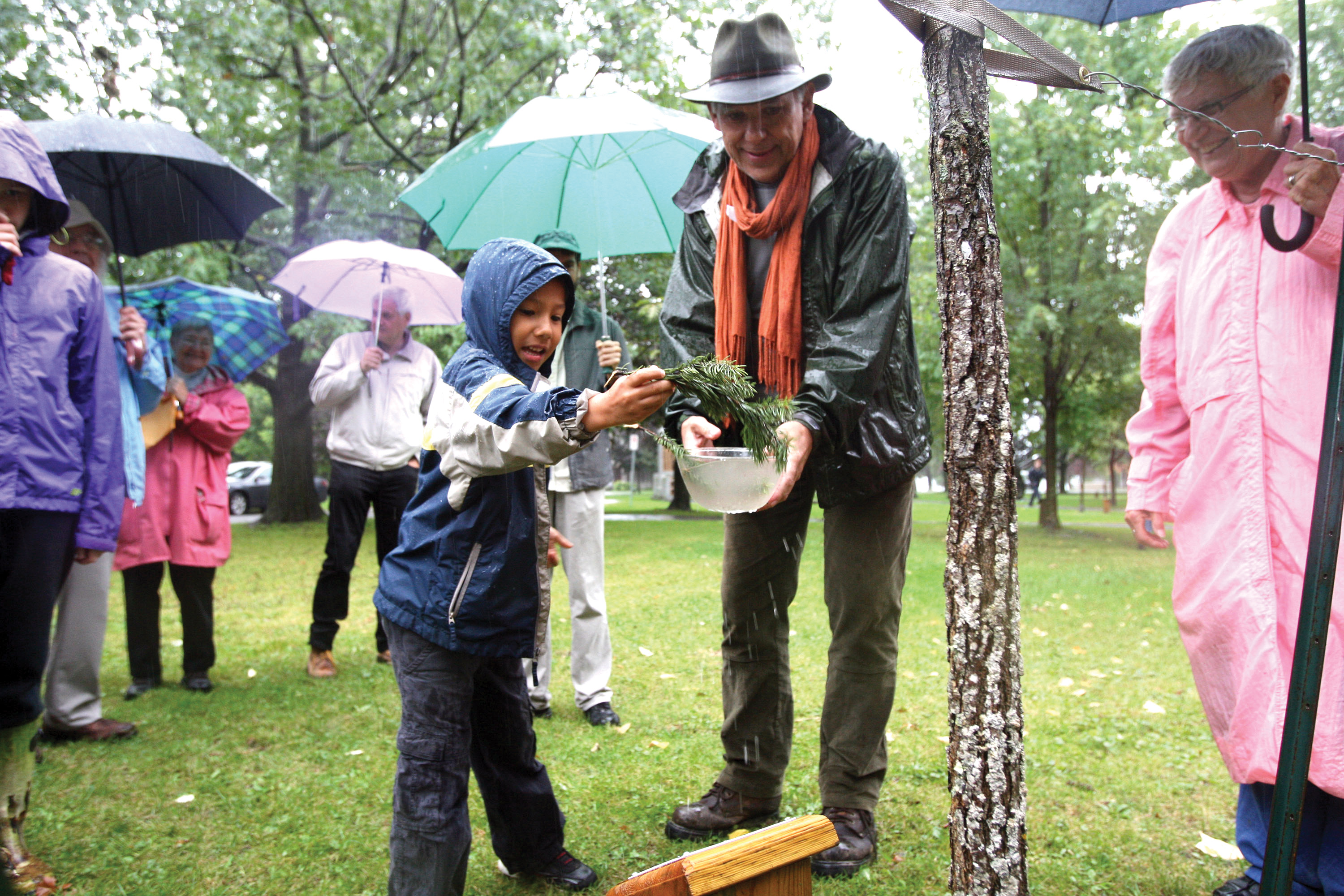 At the PeaceQuest launch last September, young Thomas McLaren, with some assistance from emcee Bill Penner, offers a few symbolic drops of water to a young oak tree planted beside the PeaceQuest marker. Despite the rain, more than 100 people gathered. Kingston, Ontario.