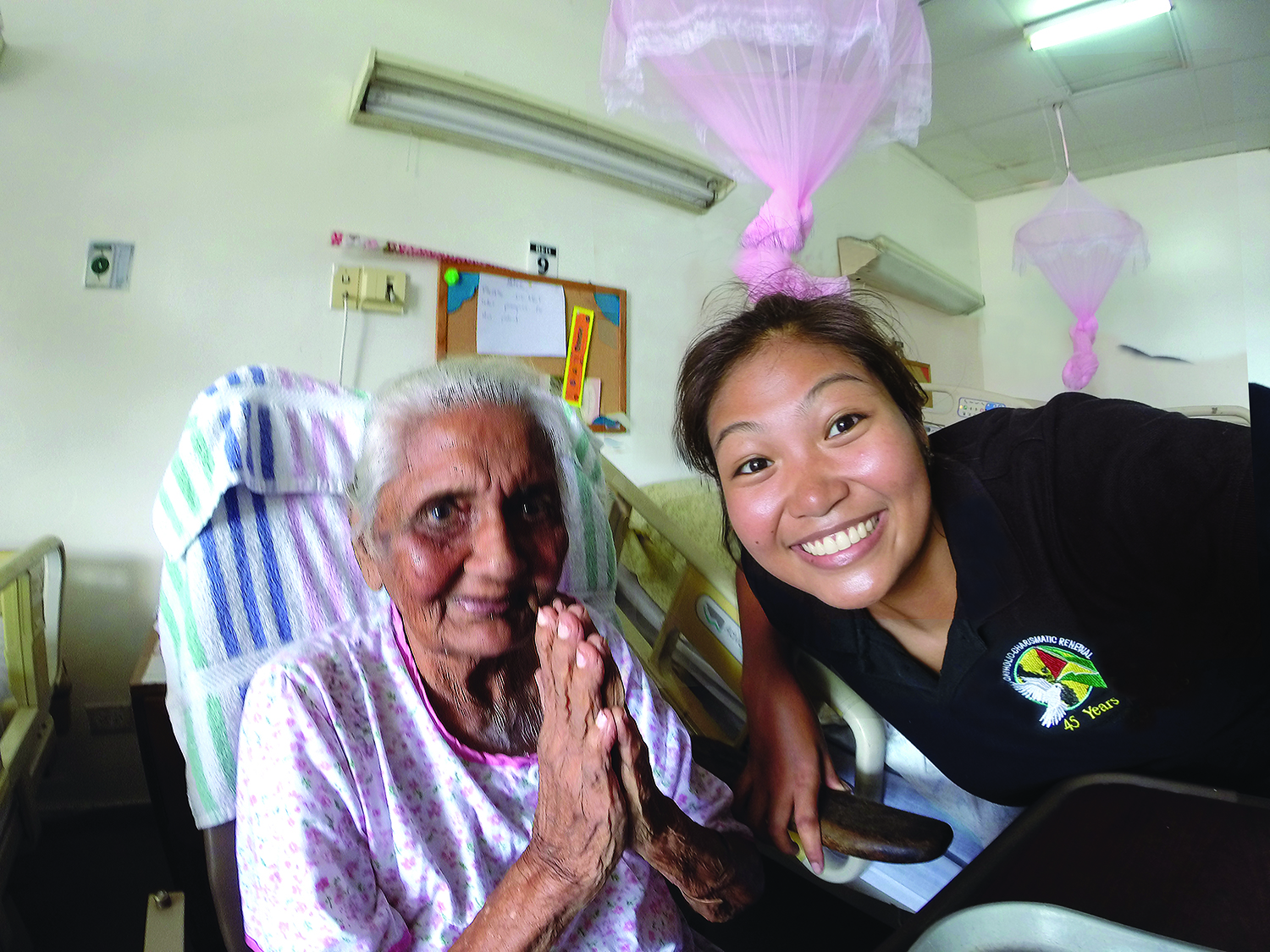 Scarboro missioner Ashley Aperocho visits a Hindu resident at a nursing home. Guyana.